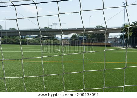 football field seen through net with stance in the back