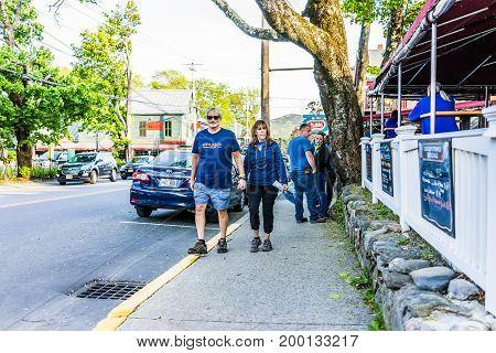 Bar Harbor USA - June 8 2017: Happy people walking on sidewalk street in downtown village in summer on main road