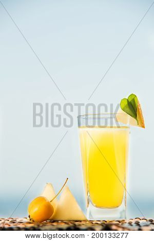 Organic melon lemonade with mineral water. Cocktail with melon juice and ice with sea on background.