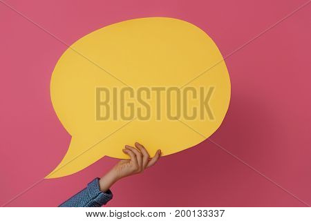 Hand with cartoon speech on colorful background. Yellow, pink and blue colors.