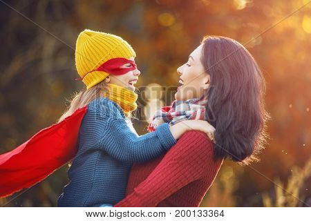 Happy family on autumn walk! Mother and daughter walking in the Park and enjoying the beautiful autumn nature. Child girl plays superhero.