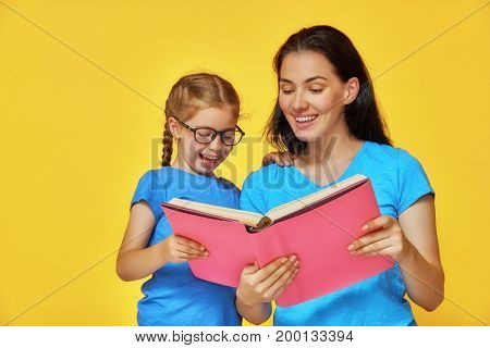 Back to school! Happy cute industrious child and her mother are reading the book indoors. Kid and adult on background of bright wall. Yellow, pink and blue color.