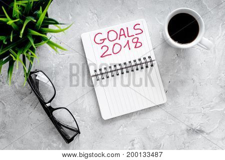 Set a goal for new year. Notebook near glasses and coffee on grey stone background top view.