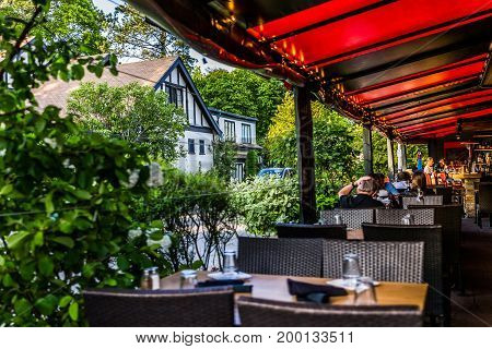 Bar Harbor USA - June 8 2017: People eating inside restaurant outdoor patio area in downtown village in summer with red color