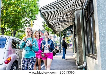 Bar Harbor USA - June 8 2017: Young girls people wearing Maine sweaters walking in downtown village in summer by stores licking ice cream spoons