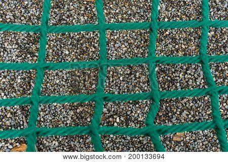 shingle seen through wide dark green net