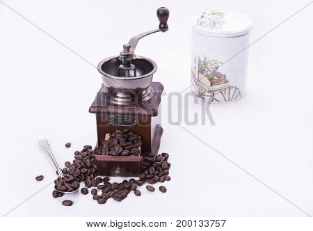 Coffee grinder full of roasted beans with spoon on white background