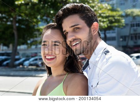 Young caucasian love couple dreaming outdoor in the city in the summer