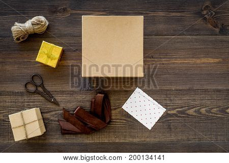 To wrap gift. Boxes, kraft paper, ribbon, sciccors on wooden background top view.