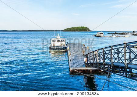 Bar Harbor USA - June 8 2017: View of dock and boat with man in downtown village in summer