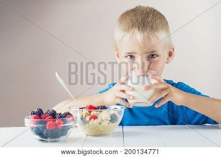 Happy boy drinking yogurt and eating porridge with berries. Looking camera. The concept of a healthy breakfast for children porridge with berries a glass of yogurt on white wooden table.