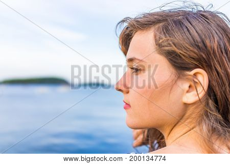 Profile Portrait Of Young Happy Smiling Woman Sitting On Edge Of Dock In Bar Harbor, Maine Looking T