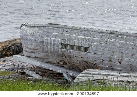 old abandoned wood boat by ocean; Fogo Island, Newfoundland