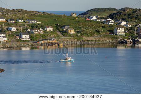 fishing boat leaving Twillingate harbor on quiet morning; Newfoundland, Canada
