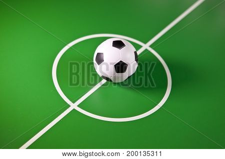 Toy soccer ball in a midfield in the center of the green field