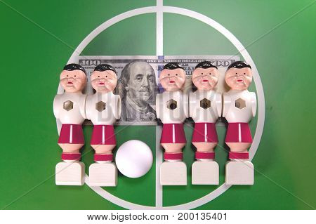 Sports and money concept-toy football players in the field and the banknote in hundred dollars on a background