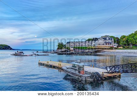 Bar Harbor USA - June 8 2017: View of dock in downtown village in summer during full moon rising at sunset twilight with police boat