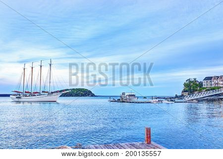 Bar Harbor USA - June 8 2017: Sunset in Bar Harbor Maine village with Margaret Todd windjammer large sailboat approaching dock