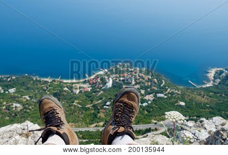 The battered trekking boots hang from the cliff against the backdrop of the green shore and the blue sea.