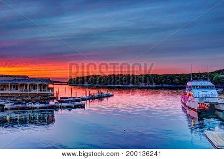 Bar Harbor USA - June 8 2017: Downtown village in summer during bright red sunset twilight with tour boat