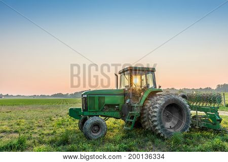 Tractor in a field on a rural Maryland farm at sunset with sun rays