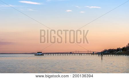A beautiful Sunset on the Chesapeake Bay in Maryland with Bay Bridge boathouse and lighthouse