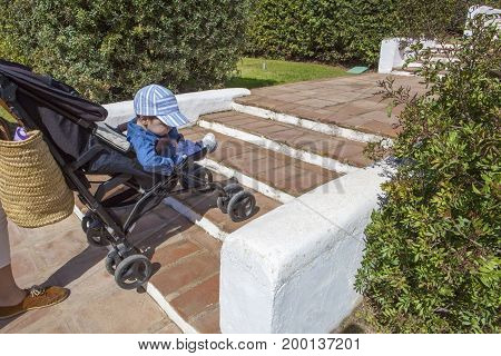 Mother carries a stroller down the stairs in garden without ramp for the disabled and baby prams