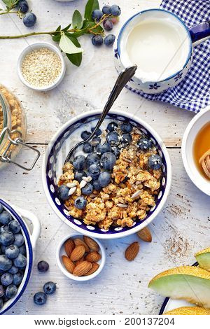 Granola with natural yogurt, fresh blueberries, nuts and honey, delicious breakfast or dessert, top view.  Healthy eating concept.
