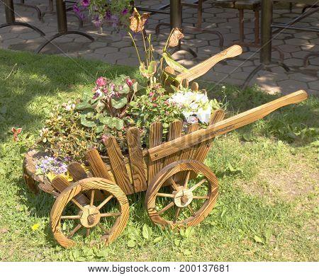 Original flowerbed made as carriage in garden.