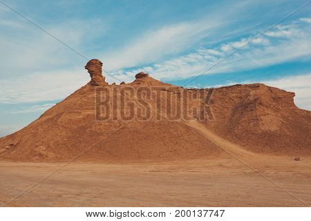 A dune landscape with stone in top in some desert