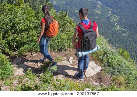 Travelers travel on the artificial roadway of the mountains reserve. Active hikers. Active and healthy lifestyle on summer vacation and weekend tour. Two young Tourists With Backpacks