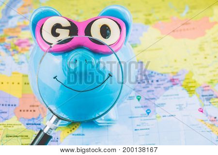 Happy piggy bank on the world map with magnifyed bright smile ready to go spend savings for next travel.