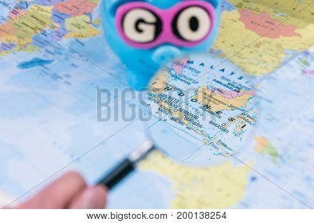 Going to Indonesia. Magnifying picked travel spot on the map. Saving piggy bank with sunglasses and GO slogan staying on the world map in background.