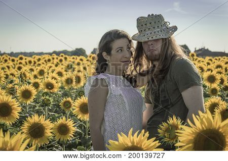 Happy spontaneous attractive young couple share a good joke laughing uproariously and hugging each other outdoors in an sunflower field
