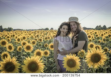 Lovely romantic caucasian couple at sunflowers field