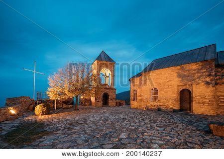 Gori, Shida Kartli Region, Georgia. St. George's Church In Bright Yellow Evening Illumination In Autumn Twilight. Travel Destination Gorijvari Church At Blue Hour