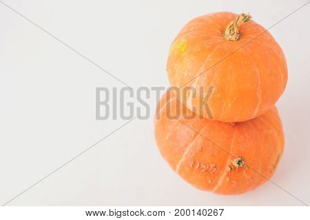Two Stacked Mini Pumpkins On White Background.