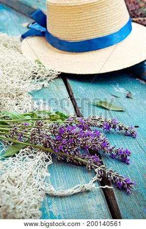 Bunch of lavender flowers fishing net and straw hat on the blue vintage wood background. Selective focus vertical.