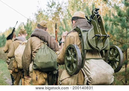 Reenactors Men Dressed As Russian Soviet Red Army Infantry Soldiers Of World War II Marching In Forest With Weapon Machine-gun At Historical Reenactment