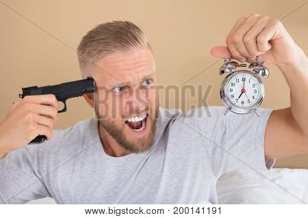 Close-up Of A Angry Young Man Holding Gun And Alarm Clock