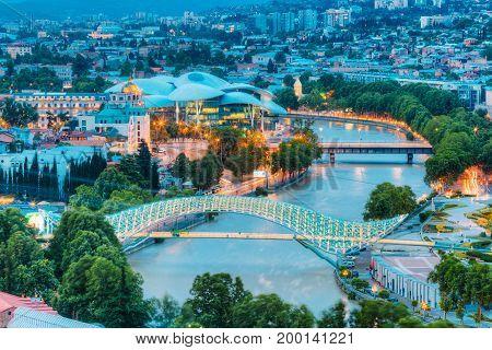 Top Illuminated Cityspape View Of Kura Mtkvari River Under Bridge Of Peace And Baratashvili Bridge, Embankment, Justice House And ity Neighborhood, Evening In Tbilisi, Georgia