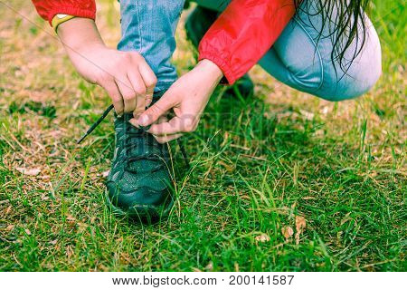 Photo of woman tying shoelaces to shoes in woods by day