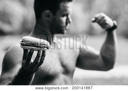 A man holds a burger and shows a biceps muscle