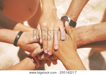 Group of Mixed Race Hipster Friends on the Beach with their Hands Stacked. Arms of Young People with on Stack. Lifestyle Team Building Concept. Phuket, Thailand.
