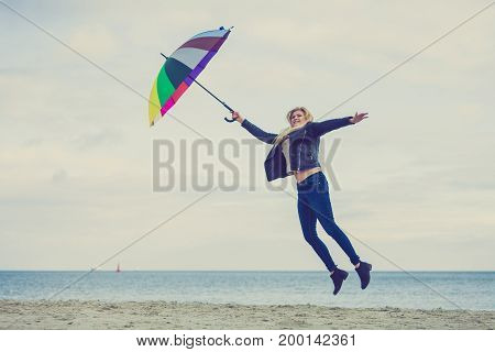 Woman Jumping With Colorful Umbrella On Beach