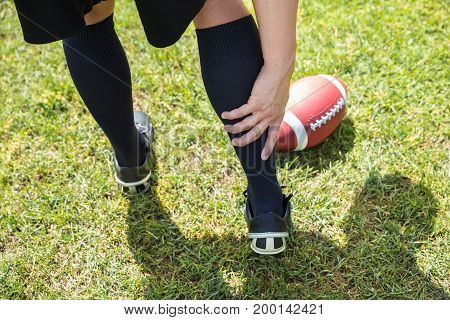 Elevated View Of American Football Player With Pain In His Lower Leg On Field