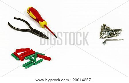 Screwdriver pliers screws and plastic dowels on a white background