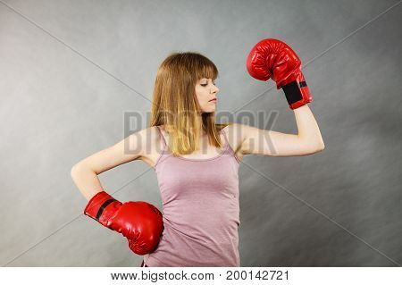 Sporty woman wearing red boxing gloves fighting. Studio shot on grey background.