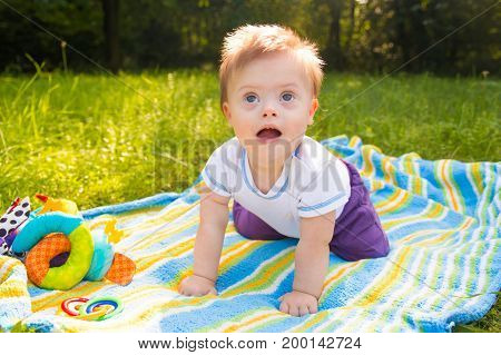 Portrait of Cute baby boy with Down syndrome lying on blanket in summer day on nature with toys