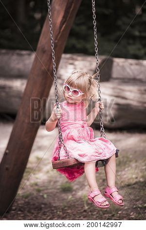 Sweet little girl dressed in a pink dress enjoys the swing on a playground on a sunny day. The picture is in pastel colors.